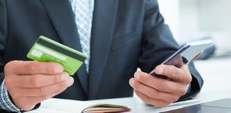 Mains masculines tenant le téléphone et la carte de crédit futés au bureau Affaires, technologie, argent liquide gratuit et conce images stock