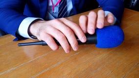 Mains masculines tenant un microphone au-dessus de la table pendant une entrevue banque de vidéos