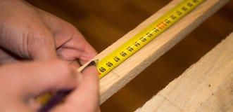 Mains masculines utilisant une roulette et un crayon faisant une marque sur la planche en bois photos stock