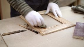Mains masculines vernissant le cadre en bois de nettoyage dans le studio de travail du bois banque de vidéos