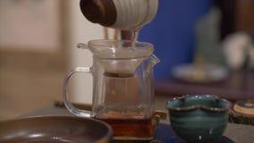Mains masculines versant le thé vert brassé dans la théière en verre avec le filtre banque de vidéos