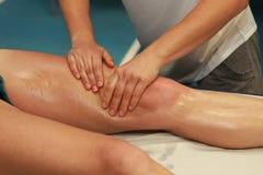 Mains massant la cuisse de l'athlète après fonctionnement Photos stock