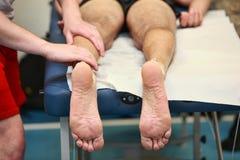 Mains massant la jambe de l'athlète après fonctionnement Image libre de droits