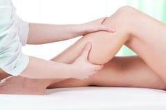 Mains massant la jambe femelle Images stock