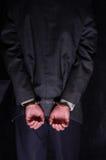 Mains menottées par homme d'affaires arrêtées au fond Photo libre de droits