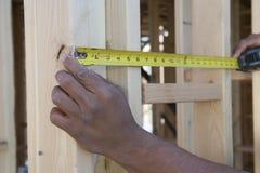 Mains mesurant entre les conseils avec le ruban métrique au site Images libres de droits
