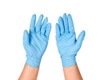 Mains mettant les gants bleus protecteurs photo stock