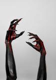 Mains minces noires ensanglantées de la mort Images stock