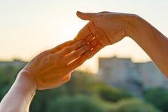 Mains montrant le geste des doigts ensemble, le symbole de l'amitié et les relations Coucher du soleil de soirée de fond, silhoue photo libre de droits
