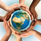 Mains multiraciales entourant le globe de la terre