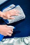 Mains nettoyant la voiture avec le décapant de jet et la serviette de microfiber Photos stock