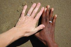 Mains noires et blanches avec des boucles Photos stock