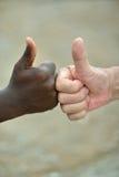Mains noires et blanches avec des pouces  Photographie stock libre de droits