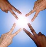 Mains noires et blanches faisant le signe de paix Photographie stock