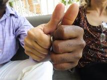 Mains noires et blanches jointives ainsi que des pouces  images stock