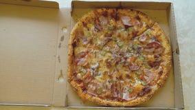 Mains ouvrant la boîte en carton de pizza banque de vidéos