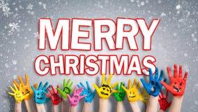 """Mains peintes d'enfants avec des smiley avec le message de """"Joyeux Noël """" photos libres de droits"""
