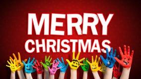 Mains peintes d'enfants avec le smiley avec le message de Joyeux Noël Photos stock