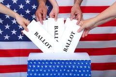 Mains plaçant des votes dans la boîte avec le drapeau américain derrière photos stock