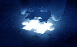 Mains plaçant la dernière partie d'un puzzle Photographie stock libre de droits