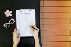 Mains plates de configuration du document remplissant d'application de visa de femme pour le voyage, portrait de lumière du solei Photographie stock libre de droits