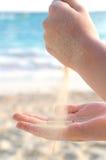 Mains pleuvant à torrents le sable sur une plage photos libres de droits