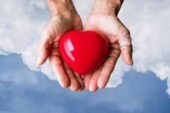 Mains pluses âgé avec la blessure tenant le coeur rouge de coeur sur le ciel bleu et les nuages blancs Photographie stock libre de droits