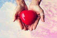 Mains pluses âgé avec la blessure tenant le coeur rouge de coeur sur le ciel coloré et les nuages blancs, ton de vintage Image libre de droits
