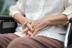 Mains pluses âgé sur un fauteuil roulant Image stock