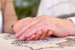 Mains pluses âgé tenant des mains du ` s de soignant images stock