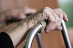 Mains pluses âgé sur un marcheur Image stock