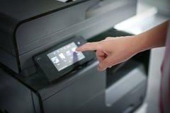 Mains poussant le bouton sur l'imprimante, vue cultivée Fermez-vous de la femme photographie stock