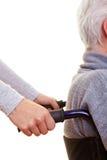 Mains poussant le fauteuil roulant Images stock