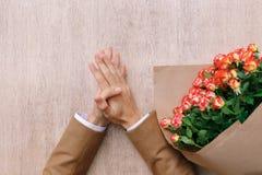 Mains précises d'homme avec la paume au-dessus de la paume et un groupe de roses Images libres de droits