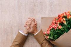 Mains précises d'homme avec les paumes croisées et un groupe de roses en Cr Photographie stock