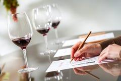 Mains prenant des notes à l'échantillon de vin Images stock