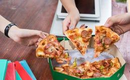 Mains prenant des tranches de pizza Photographie stock libre de droits