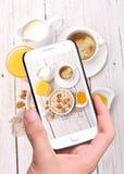 Mains prenant le petit déjeuner de photo avec le smartphone photos stock