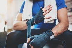 Mains prepairing d'homme musculaire de boxeur pour le stage de formation kickboxing dur dans le gymnase Jeune athlète attachant l photos stock