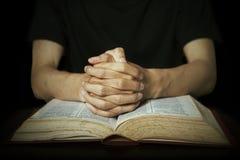 Mains priant sur la bible photographie stock libre de droits