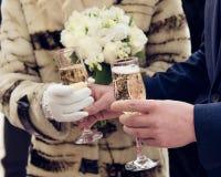 Mains qui jugent le champagne en verre dans un mariage Image libre de droits