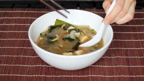 Mains remuant la soupe miso avec la cuillère, sélectionnant le tofu avec des côtelettes banque de vidéos