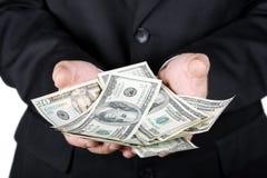 Mains retenant des dollars Photographie stock libre de droits