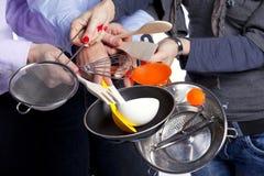 Mains retenant des outils de vaisselle de cuisine Photographie stock libre de droits