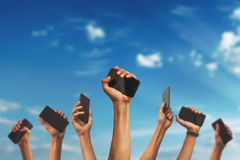 Mains retenant des téléphones images stock