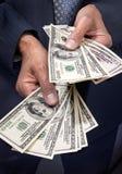 Mains retenant l'argent des dollars Images libres de droits