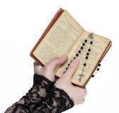 mains retenant la bible et priant avec un rosaire Images libres de droits