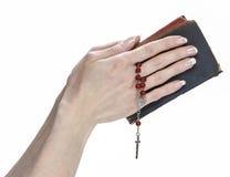 mains retenant la bible et priant avec un rosaire Photographie stock libre de droits