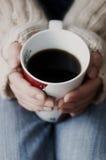 Mains retenant la cuvette de café foncé Image stock