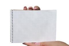 Mains retenant le carnet de notes à spirale blanc Photo stock